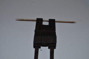 """Die zweite Laserkanone dann auch an dem Balken fixieren. Die Zahnstocher dienen hier noch dazu, die Kanonen """"in Form"""" zu halten, damit die Bohrungen übereinander liegen."""